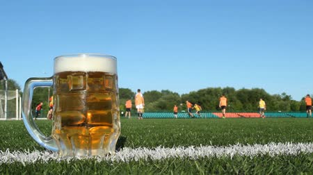 A glass of beer stands on the green grass on a football field, players play football