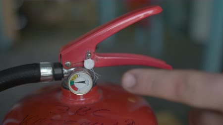 hand indicates a pressure indicator gauge in the fire extinguisher, close up Stok Video