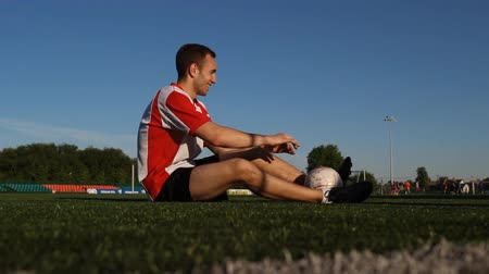 striker : Player is sitting on the grass and smiling
