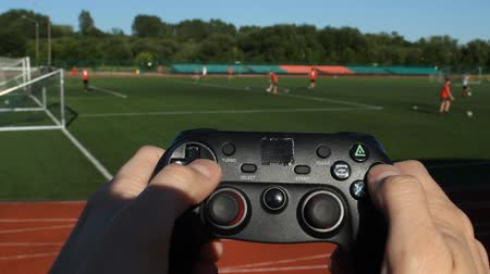 umma : Mens hands hold a game joystick and press buttons on the background of the stadium in which they play football Stok Video
