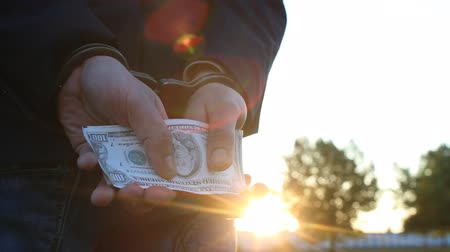 kajdanki : A man in a jacket holds money dollars in handcuffs, close-up, sunset