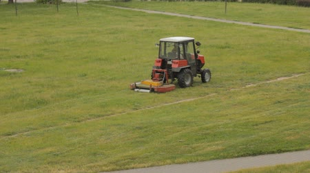 садовник : Old tractor mows the lawn, the overall plan Стоковые видеозаписи