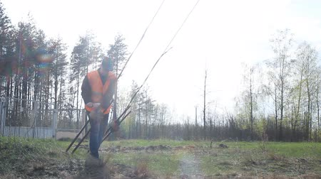 fitter : worker in the signal jacket performs work near the power station Stock Footage