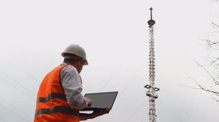 telephone tower : A man inspector enters data into the laptop and looks at the telephone tower