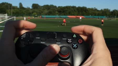 umma : The man clicks on the buttons in the game joystick on the background of the stadium and the game of football, close-up