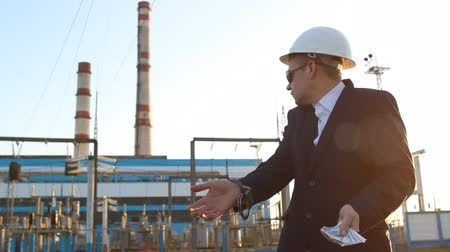 kajdanki : The engineer inspector in handcuffs keeps money against the background of the power plant and is indignant