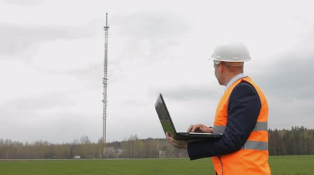 yelek : A man in a helmet inspector with a laptop records the data checks and looks toward the telephone tower