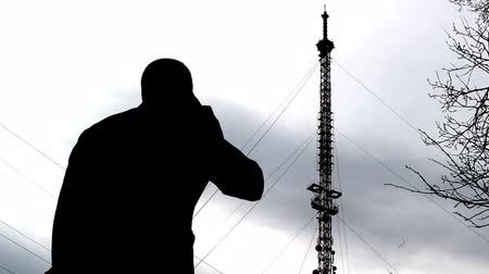 inspector : A man talking on the phone in the background a telephone tower, a mobile network check