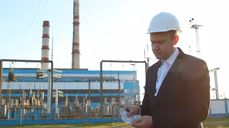 legfőbb : engineer chief counts money dollars against a power plant Stock mozgókép
