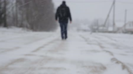 andar : A man with a backpack walks down the street, a heavy snowfall winter, a blurry Vídeos