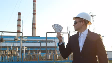 łapówka : A young satisfied engineer inspector in black glasses with money dollars against a power plant background