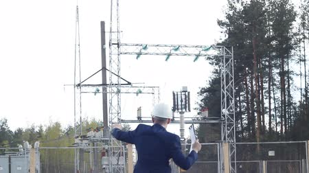 voltů : a young engineer inspector dances and rejoices against the background of a power plant