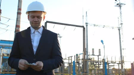 voltů : engineer chief counts money dollars against a power plant Dostupné videozáznamy