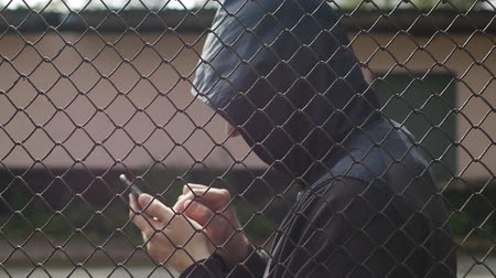 bandido : Hacker burglar is climbing in the phone in jail behind bars, close-up, arrest, computer technology, hacking Stock Footage