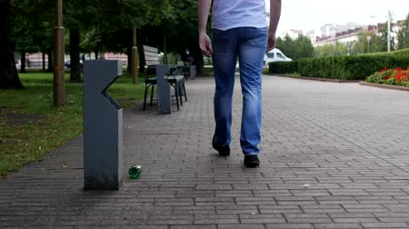 wysypisko śmieci : A young man throws a plastic bottle in the city near a trash can, a passer-by goes and picks up trash after him and throws it into the trash