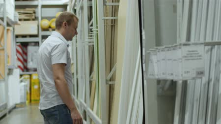 laminált : male buyer chooses laminate in shop of building materials
