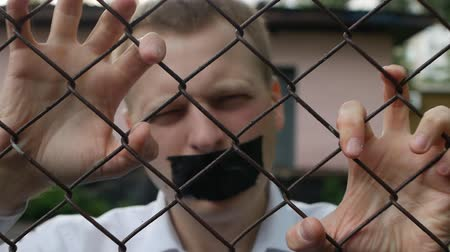 political prisoner : The man behind the bars with his mouth taped and shouting with his hands on the grille, close-up, slow-mo, disclosure of information