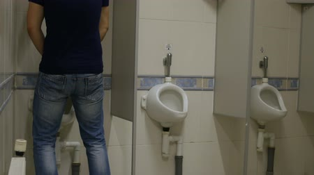 prostata : man with urinary incontinence runs to the urinal in public restroom