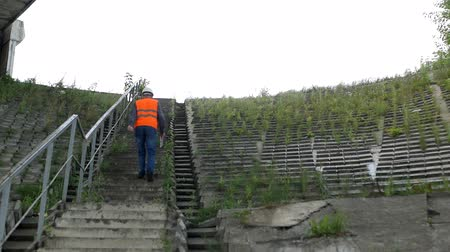 bridgework : The architect climbs the stairs to assess the condition of the bridge and the construction, inspector