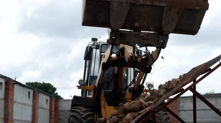 buldozer : A large loader pours out ladle stones with sand on the seed drill to separate the sand from the stones, sower