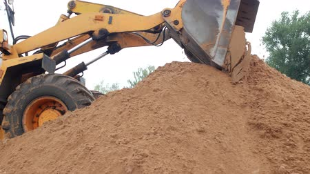 taş ocağı : A large yellow loader pours out a bucket of earth, ground loader Stok Video