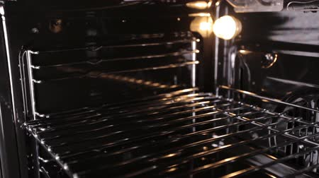 gas hob : A modern gas cooker with an oven in which a light is burning, a view inside, a close-up Stock Footage