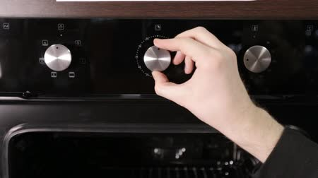 rukojeť : A man puts out the temperature twist the handle in a modern gas stove, close-up, modern gas cooker Dostupné videozáznamy