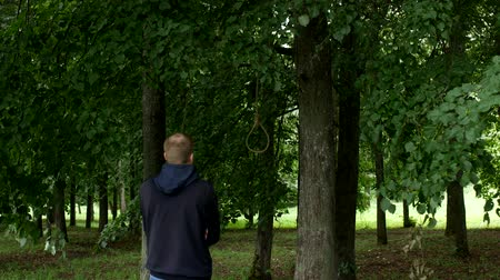 por cento : A man stands and looks at a noose with a rope that hangs on a tree, thinks about hanging suicide, hang oneself