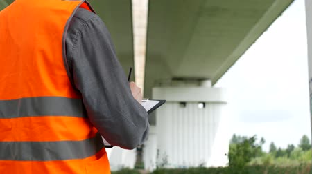 construtor : the inspector records the violations found during the inspection of the bridge across the river, close-up, examiner and bridgework