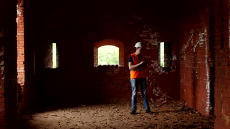 rekonstrukce : A young inspector checks the walls of an ancient building, historian