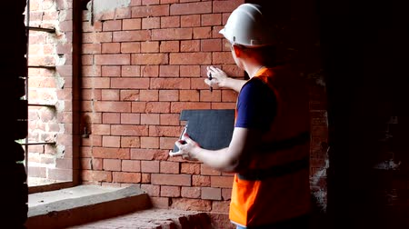 supervising : The man the historian examines the walls of the old building, checks the density of the brick, preparation for reconstruction Stock Footage