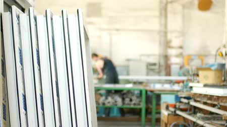pvc frames : The production of assembling and manufacturing pvc windows, the shop with finished products, in the background, the worker sets the workpiece profile in the machine, workman