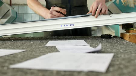 pvc frames : Production and manufacturing of pvc windows, a male worker is measuring a pvc profile piece and marking with a marker, tape-measure Stock Footage