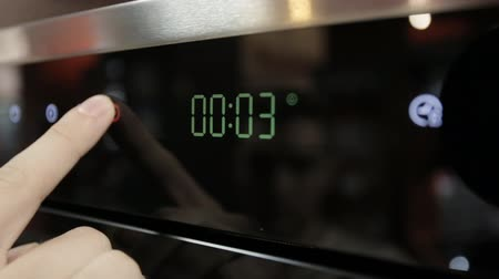 cooktop : A man adjusts time in a modern gas stove, close-up, time