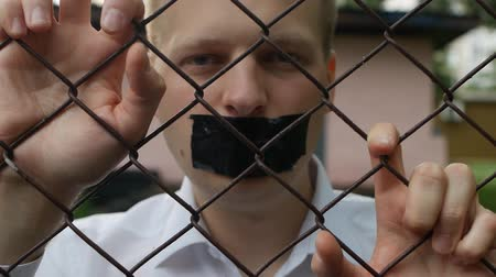 political prisoner : A man is behind bars and looks at the camera, information is not disclosed, freedom of speech, close-up, slow motion