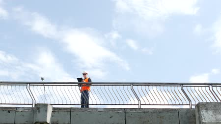 посетитель : A man inspector walks across the bridge looking around and inspects the quality of the bridge, checks, engineer