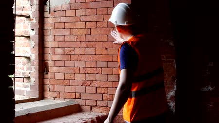 yoğunluk : Young inspector checks the density of brick walls, preparation for reconstruction, architect Stok Video
