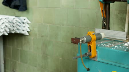 workman : Production and manufacturing of pvc windows, a female worker installs a pvc profile in the machine and drills a hole under the handle, close-up, drill bench Stock Footage