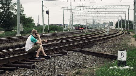 crossway : man is sitting on the railway or railroad and talkIng on the smartphone, life threatening Stock Footage