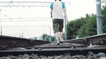 crossway : man with headphones walks along the railway, dangerous for life