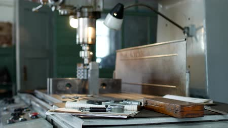 repairer : A private workshop for working with metal parts, in the background a drilling machine drills a hole in the pulley, on the table lie measuring tools, production, small business Stock Footage