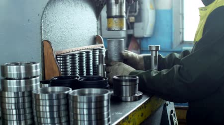 franzir : The worker assembles the pressing of the bearing into a metal clip on the machine, assembles the finished unit, close-up, press, ferreous Stock Footage
