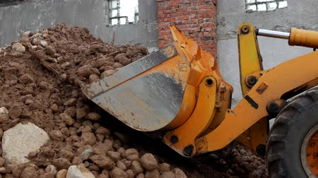 buldozer : A yellow pusher gathers stones with sand into a sifting bucket, a close-up, loader and stones