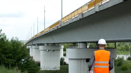 bridgework : A man architect examines the state of the bridge over the river and records the data, bridgework