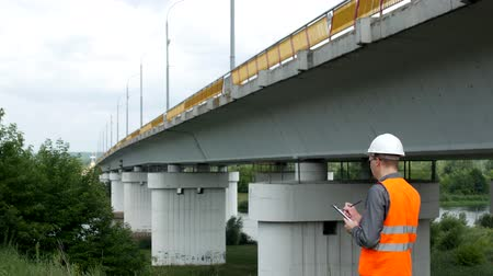 bridgework : The architect checks the state of the bridge across the river, records downsides, examiner and inspector