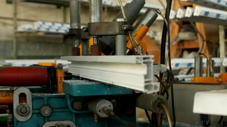 double glazed windows : Production and manufacturing of pvc windows, male worker drills holes on a drilling machine in a pvc profile for manufacturing a pvc window, close-up, bench