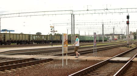 safeness : A young man in headphones crosses the railway tracks and listens to music, does not hear the approaching train