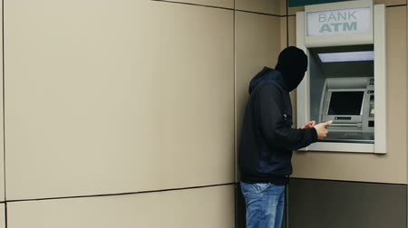 card pin : Hacker or thief with smartphone steals information or data from bank ATM