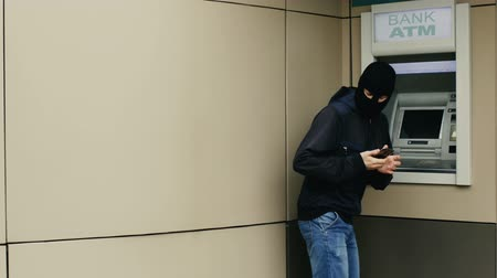 chip and pin : Criminal or hacker in a mask and with smartphobe hacks out an bank ATM Stock Footage
