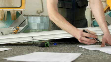 pvc frames : Production and manufacturing of pvc windows, a male worker is measuring a pvc profile piece and marking with a marker, tape-measure and marker Stock Footage